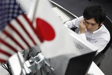 Дилер следит за курсами валют в Токио, 26 июля 2011 года. Азиатские фондовые рынки, кроме Южной Кореи, выросли в понедельник благодаря ослаблению иены и локальным факторам. REUTERS/Yuriko Nakao