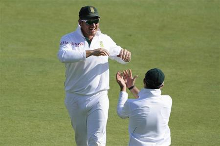 South African captain Graeme Smith (L) celebrates with Dean Elgar after Elgar took a catch to dismiss Pakistan's Sarfraz Ahmed (unseen) during the third day of the third test cricket match in Pretoria, February 24, 2013. REUTERS/Ihsaan Haffejee