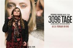 "Austrian kidnap victim Natascha Kampusch poses in front of a film poster before the premiere of the film ""3,096 Days"" in a cinema in Vienna February 25, 2013. A new film based on the story of Kampusch shows her being repeatedly raped by captor who beat and starved her during the eight-and-a-half years that he kept her in a cellar beneath his house. REUTERS/Herwig Prammer"