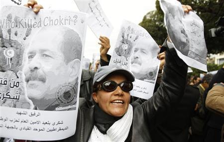 A woman chants slogans and holds pictures of assassinated leftist politician Chokri Belaid during a demonstration against the Islamist Ennahda movement in Tunis February 23, 2013. REUTERS/Zoubeir Souiss