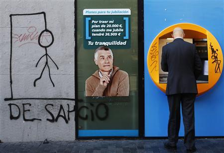 A man uses an ATM machine at a La Caixa savings bank branch close to a drawing of a hangman with the word ''Desahucio'' (eviction) spelled out, in central Madrid in this November 19, 2012 file photo. REUTERS/Juan Medina/Files