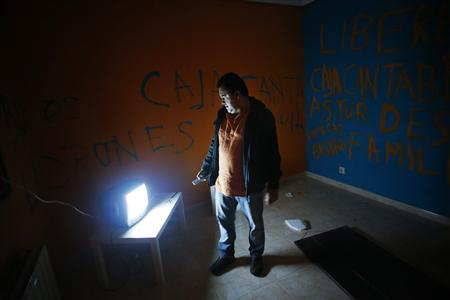 Juan Carlos Castano, 43, turns on the TV in his emptied-out bedroom as he waits for the judicial commission to carry out his eviction in Madrid in this September 28, 2012 file photo. Castano, a Spanish national who came from his native Colombia to Spain in 2000, stopped making mortgage payments after becoming unemployed in late 2009. For more than a century, Spanish law has determined that if a person borrows money to buy a home, they can only be freed of the debt when it is repaid. Even in death, the debt is not cancelled. As the country enters another year of recession, calls are mounting for the system to be relaxed. But the banks worry this would damage their access to funds. Picture taken September 28, 2012. To match Insight SPAIN/MORTGAGE-REFORM REUTERS/Susana Vera/Files (SPAIN - Tags: BUSINESS POLITICS REAL ESTATE)