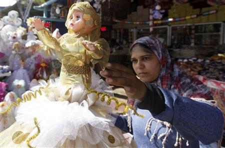 An Egyptian woman shops for a traditional doll dressed as a bride wearing a hijab, ahead of Moulid al-Nabi, the birthday of Prophet Mohamed, in old Cairo January 22, 2013. REUTERS/Amr Dalsh