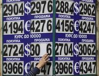 """Человек меняет цифры на табло с курсами валют в Москве, 10 августа 2011 года. Рубль подрос к валюте США, торгуется с незначительной прибылью к бивалютной корзине на биржевой сессии среды, отражая текущее подобие стабилизации глобальных рынков после """"голубиных"""" комментариев главы ФРС Бена Бернанке и сильных данных о недвижимости в США, но при сохранении настороженного отношения к проблемам еврозоны после неоднозначных парламентских выборов в Италии. REUTERS/Sergei Karpukhin"""