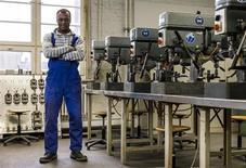 Alemania buscó el miércoles facilitar el empleo de trabajadores calificados de fuera de la Unión Europea, intentando aliviar una escasez crónica en áreas como ingeniería, conducción ferroviaria y plomería. En la imagen, el aprendiz británico de ingeniero Gabriel Ahimah Vijent en un taller del centro de formación de Siemens en Berlín, el 26 de febrero de 2013. REUTERS/Thomas Peter