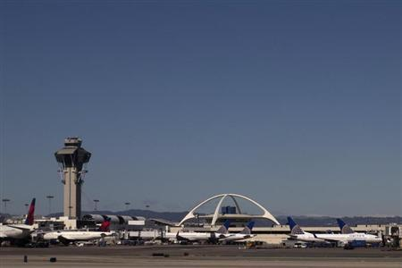 United Airlines planes are seen in the foreground of the Los Angeles International Airport (LAX) and its air traffic control tower on February 20, 2013. REUTERS/Adrees Latif
