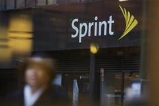 People walk past a Sprint store in New York December 17, 2012. Clearwire Corp agreed to sell roughly half of the company for $2.2 billion to majority shareholder Sprint Nextel Corp, which would have full ownership of spectrum that will help offer high-speed wireless services. REUTERS/Andrew Kelly
