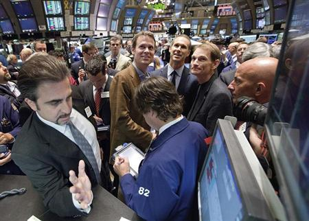 Tim Westergren (top center-left), founder and Chief Strategy Officer, and Joe Kennedy (top center-right), president and CEO of Pandora internet radio, watch as their company begins trading on the floor of the New York Stock Exchange June 15, 2011. REUTERS/Ben Hider-NYSE Euronext