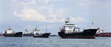 Нефтеналивные танкеры у берегов Сингапура 18 апреля 2012 года. Цены на нефть Brent держатся вблизи $112 за баррель после того, как глава ФРС вновь заверил рынки в приверженности центробанка экономическим стимулам, а Италия успешно провела аукцион облигаций несмотря на опасения политического тупика. REUTERS/Tim Chong