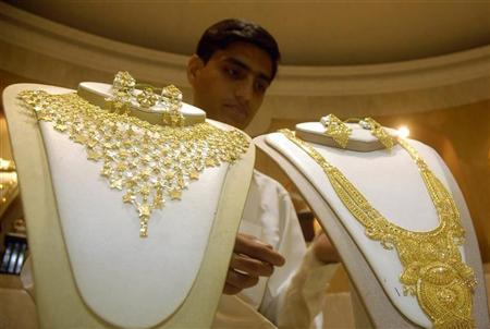 A salesman arranges gold necklaces at a jewellery shop in Agartala October 25, 2008. REUTERS/Jayanta Dey/Files