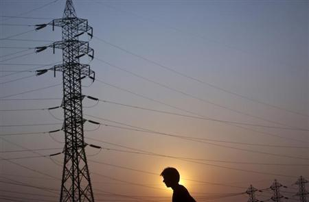 A man walks under high-tension power lines on the outskirts of Mumbai February 13, 2013. REUTERS/Vivek Prakash
