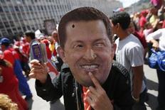 Сторонник венесуэльского президента Уго Чавеса в маске с его изображеием на уличной акции в Каракасе 27 февраля 2013. Чавес будет излечен и вернется к активной деятельности, полагают 60 процентов жителей Венесуэлы, хотя лежащий в больнице президент страны практически не появлялся в СМИ два с половиной месяца, свидетельствует опрос, опубликованный во вторник. REUTERS/Jorgre Silva