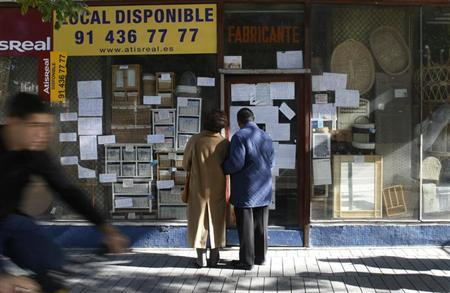 People stop to read the discount signs of a store that is going out of business in downtown Madrid November 14, 2008. REUTERS/Susana Vera