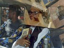 Delwar Hossain Sayedee (R), 73, vice-president of the Jamaat-e-Islami party, sits inside a vehicle next to a police officer on his way to a court in Dhaka February 28, 2013. A Bangladesh tribunal sentenced an Islamist party leader to death on Thursday, the third verdict by the court set up to investigate abuses during the country's independence war, and two people were killed in protests by his supporters. Sayedee was found guilty of charges of mass killing, rape, arson, looting and forcing minority Hindus to convert to Islam during the 1971 war of independence from Pakistan, lawyers and tribunal officials said. REUTERS/Stringer