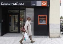 Al menos tres bancos españoles, entre los que estarían Santander, Sabadell y Popular, presentaron el jueves una oferta no vinculante por Catalunya Banc, dijeron varias fuentes conocedoras de la operación. Este jueves expiraba el plazo para la presentación de ofertas no vinculantes por la deficitaria entidad catalana que en principio prevé estar cerrado en el primer trimestre de este año, explicó una de las fuentes. en la imagen, una mujer camina junto a una sucursal de la nacionalizada Catalunya Caixa en Vilassar de Mar, Barcelona, el 28 de noviembre de 2012. REUTERS/Gustau Nacarino