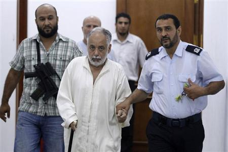 Deposed Libyan leader Muammar Gaddafi's former prime minister Al Baghdadi al-Mahmoudi (C) is escorted in the office of his prison guard in Tripoli after being extradited from Tunis June 24, 2012. REUTERS/Anis Mili