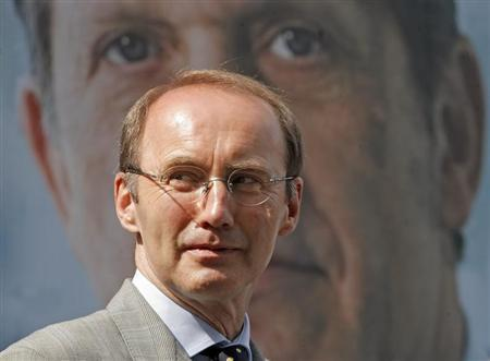Austrian People's Party (OeVP) candidate for European parliament elections Othmar Karas poses in front of an election poster depicting top candiate Ernst Strasser in Vienna May 11, 2009. REUTERS/Heinz-Peter Bader