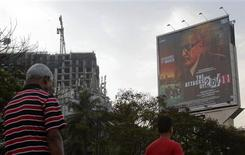 "People walk underneath a promotional billboard for Ram Gopal Varma's film ""The Attacks of 26/11"" by a roadside in Mumbai February 28, 2013. REUTERS/Vivek Prakash"