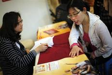 A job seeker (R) attends a work interview during a job fair at a convention center in Shanghai April 7, 2012. REUTERS/Carlos Barria