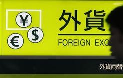 Мужчина проходит мимо обменного пункта в аэропорту в Токио, 1 августа 2011 года. Курс иены растет в понедельник за счет падения китайских акций после решения Пекина ввести существенные ограничения в секторе недвижимости. REUTERS/Yuriko Nakao