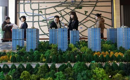 Visitors look around a miniature of new apartment complex at a showroom in Beijing February 27, 2013. REUTERS/Kim Kyung-Hoon