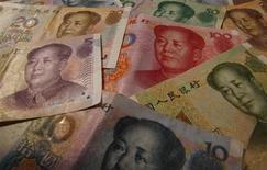 Банкноты юаня в Шанхае 15 апреля 2012 года. Китай собирается использовать растущие иностранные вложения в юань объемом около 1 триллиона юаней ($160 миллиардов), чтобы оправдать знаковый сдвиг в тактике ослабления контроля за капиталом. REUTERS/Petar Kujundzic