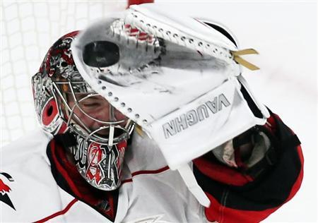 Carolina Hurricanes goalie Cam Ward makes a glove save against the Montreal Canadiens during third period NHL hockey action in Montreal, February 18, 2013. REUTERS/Christinne Muschi