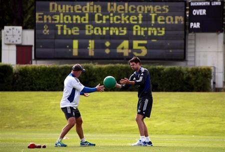 England cricket team player James Anderson (R) throws a ball to a team trainer during a cricket training session at the University Oval in Dunedin March 4, 2013. REUTERS/David Gray