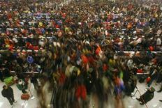 Пассажиры выходят с железнодорожной станции в Ухане в день окончания новогодних каникул 9 февраля 2011 года. Китай поставил свой быстрорастущий потребительский класс во главу угла: уходящий премьер-министр Вэнь Цзябао во вторник представил план реформ, направленных на более равномерное распределение плодов экономического роста в стране, где проживают 1,3 миллиарда человек. REUTERS/Stringer