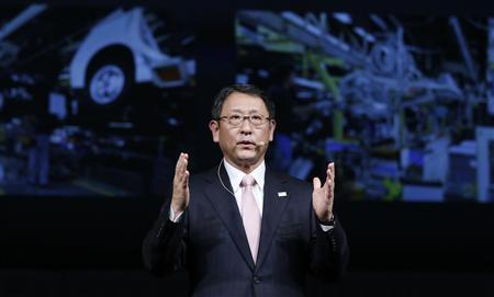 Toyota Motor Corp President Akio Toyoda speaks in front of images of the company's factory during a news conference in Tokyo in this December 25, 2012 file photo. REUTERS/Yuriko Nakao/Files