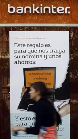 A woman walks past a Bankinter bank office branch in Madrid April 24, 2009. REUTERS/Susana Vera