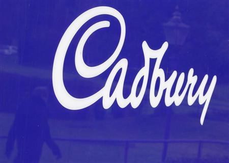 A man is reflected in a sign outside the Cadbury factory in Bournville, central England, January 19, 2010. REUTERS/Darren Staples