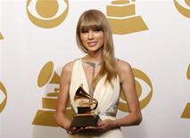 """Taylor Swift holds the award for Best Song Written For Visual Media for """"Safe & Sound"""" backstage at the 55th annual Grammy Awards in Los Angeles, California February 10, 2013. REUTERS/Mario Anzuoni"""