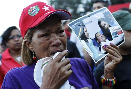 Supporters of Venezuela's President Hugo Chavez react to the announcement of his death outside the hospital where he was being treated, in Caracas, March 5, 2013. REUTERS/Carlos Garcia Rawlins