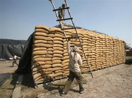 A worker carries a ladder past sacks filled with wheat at a Food Corporation of India (FCI) warehouse in Morinda in Punjab February 20, 2013. REUTERS/Ajay Verma/Files