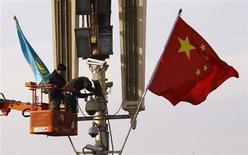 Рабочие проверяют камеры безопасности на столбе, на котором установлены флаги Казахстана и Китая, на площади Тяньаньмэнь в Пекине 31 марта 2012 года. Казахстан наращивает поставки нефти в Китай в 2013 году, постепенно разворачивая экспорт на восток вместо загрузки трубопроводной системы России - своего партнёра по Таможенному союзу. REUTERS/David Gray