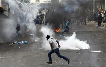 A stone-throwing Palestinian runs past tear gas fired by Israeli soldiers during clashes that broke out after the funeral of a Palestinian prisoner in an Israeli jail, in the West Bank city of Hebron, in this February 25, 2013 file photo. REUTERS-Ammar Awad-Files