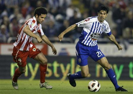 Deportivo La Coruna's Juan Carlos Valeron (R) fights for the ball with Atletico Madrid's Suarez during their Spanish First Division match at Riazor stadium in Coruna April 30, 2011. REUTERS/Miguel Vidal