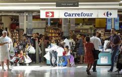 Carrefour à suivre à la Bourse de Paris. Le géant de la distribution signe la plus forte hausse du CAC 40 car ses résultats annuels illustrent un redressement de ses performances en France et une baisse de la dette, ce qui va lui permettre d'accélérer le rythme de ses investissements en 2013. /Photo prise le 29 août 2012/REUTERS/Charles Platiau
