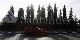 A car drives past the logo of Spanish Santander bank in a roundabout outside the company's headquarters in Boadilla del Monte, outside Madrid, January 31, 2013. REUTERS/Sergio Perez