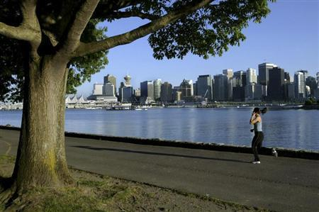 A jogger runs along the seawall in Stanley Park with the city skyline in the background in this June 24, 2003 file photo. REUTERS/Andy Clark/Files