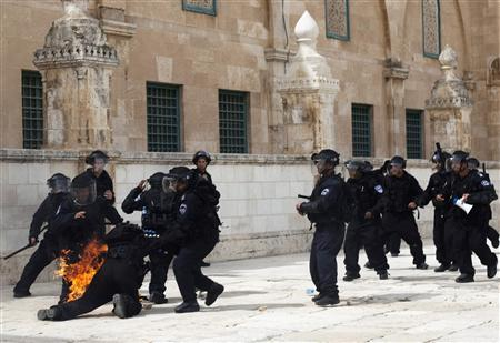 An Israeli police officer falls, engulfed in flames after Palestinian protesters threw firebombs during clashes after Friday prayers at a compound known to Muslims as al-Haram al-Sharif and to Jews as Temple Mount, in Jerusalem's Old City March 8, 2013. Israeli police fired stun grenades to disperse Palestinian worshippers who had thrown rocks and firebombs at them after Friday prayers at the al-Aqsa Mosque compound in Jerusalem's Old City, police said. REUTERS/Mostafa Alkharouf