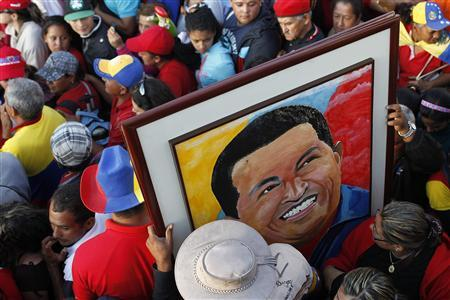 Supporters of Venezuela's late President Hugo Chavez hold a portrait of him as they wait for a chance to view his body lying in state, at the military academy in Caracas March 8, 2013. REUTERS/Carlos Garcia Rawling