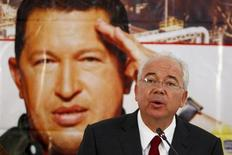 Venezuela's Energy Minister Rafael Ramirez talks to the media in front of a giant picture of Venezuela's President Hugo Chavez during a news conference at the headquarters of the state-run oil company PDVSA in Caracas February 13, 2013. REUTERS/Carlos Garcia Rawlins