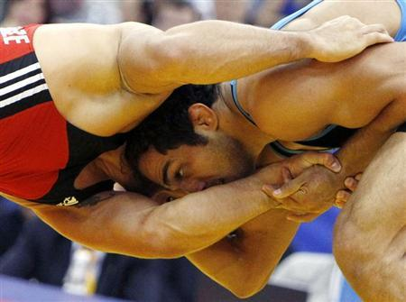 Georgia's George Goghelidze challenges Iran's Arfan Moradali Amiri (red) during their 96kg men's freestyle bronze medal match at the World Wrestling Championships in Moscow September 11, 2010. REUTERS/Grigory Dukor