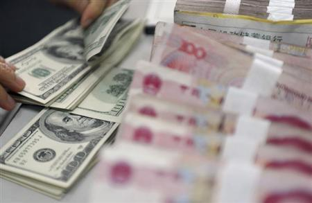 A clerk counts U.S. dollar banknotes after counting Chinese 100 Yuan banknotes at a branch of the Agricultural Bank of China in Qionghai, China's southmost Hainan province, November 12, 2012. REUTERS/China Daily