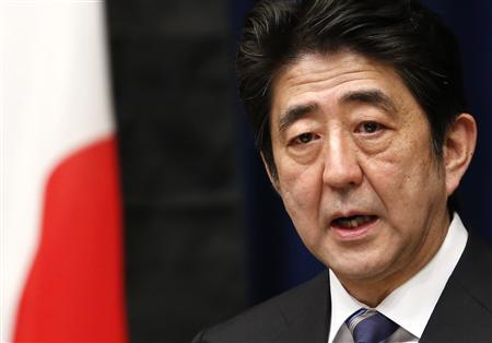 Japan's Prime Minister Shinzo Abe speaks next to the national flag, which is hung with a black ribbon as a symbol of mourning for victims of the March 11, 2011 earthquake and tsunami, during his news conference at his official residence in Tokyo March 11, 2013. REUTERS/Yuya Shino