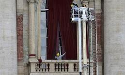 Workers put up a red curtain on the central balcony, called the Loggia of the Blessings, of Saint Peter's Basilica at the Vatican March11, 2013. Roman Catholic Cardinals will begin their conclave inside the Sistine Chapel on Tuesday to elect a new pope. REUTERS/Dylan Martinez