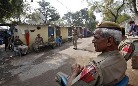 Police sit inside the Ravi Das camp, the slum where four of the six accused in a rape case including Ram Singh reside at, in New Delhi March 11, 2013. REUTERS/Mansi Thapliyal