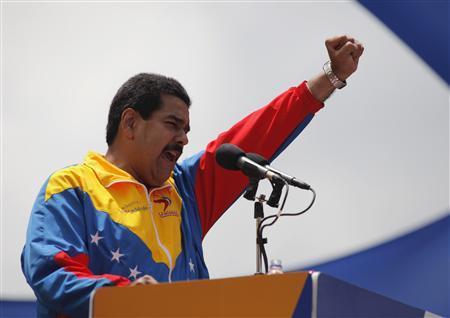Venezuela's acting President Nicolas Maduro gestures to supporters after he registered as a candidate for president in the April 14 election outside the national election board in Caracas March 11, 2013. REUTERS/Marco Bello